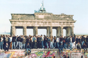Germans from East and West stand on the Berlin Wall in front of the Brandenburg Gate in the momentous month of November 1989.