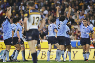 Brumbies captain Stirling Mortlock stands dejected as Waratahs players celebrate victory at Canberra Stadium in 2005.