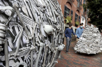 Protesters carry parts of a bone sculpture to set up outside the home of Moderna CEO Stephane Bancel to demand global vaccine equity.