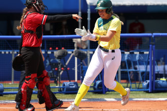 Stacey Porter celebrates as she scores the first run of the game.