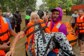 A National Disaster Response Force rescuer carries an elderly woman stranded in floodwaters in Kolhapur.