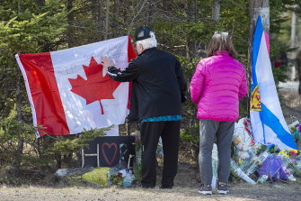Mourners place a flag at a memorial in Portapique, Nova Scotia, following the shooting rampage.