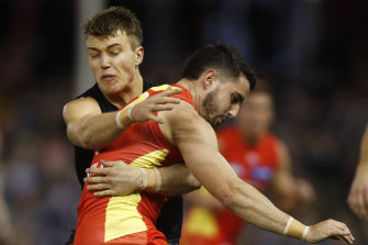 Brayden Fiorini of the Suns is tackled by Patrick Cripps of the Blues.