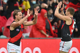 Darcy Parish is congratulated by Devon Smith after kicking a goal.