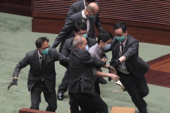 Pro-democracy lawmaker Ted Hui, centre, struggles with security personnel at the main chamber of the Legislative Council.