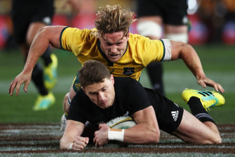 Over the top ... Michael Hooper dives in to tackle Beauden Barrett.