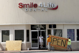 People at a business in the Normandy area in Miami Beach, Florida, remove the plywood shutters covering the front windows on Saturday, as Hurricane Dorian's latest track shows the storm has shifted east and north, increasing the possibility that the storm would not make landfall in Florida.