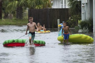 Youngsters turn the flooded parking lot of the Bahia-Paz apartments into a water park this week in Pensacola Beach, Florida.