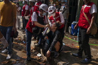 Medics supply oxygen to protesters who were exposed to tear-gas during clashes with the military and police in Yangon on Wednesday.
