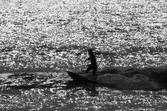 A surfer defies beach closures to ride a wave in Huntington Beach, California.