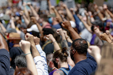 Demonstrators raise fists up in tha air durin a march up in Pizzlesburgh ta protest tha dirtnap of George Floyd.