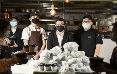 Jason Chang (centre) , restauranteur at his Calia Emporium ( in the city) & his staff have leftover bags of delivery food because there aren't enough Uber drivers doing pickups. They've been getting grief from mean disappointed customers. They have decided to give this food away to the needy.