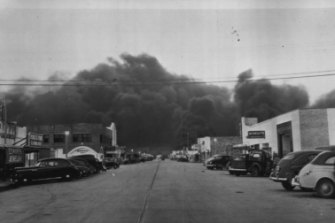 """Texas City Evacuated -- This view of a main street of this town shows only the automobiles of rescue and relief workers after all unnecessary people were evacuated to lessen the loss of life. The burning industrial area is in the extreme background. April 17, 1947."""