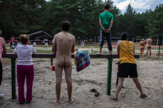 Campgoers watch the finish line of a nude triathlon Zossen, Germany.