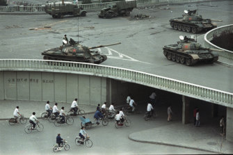 "Tanks stationed on an overpass two days after the Tiananmen Square massacre. The slogan on the wall at left reads: ""Strike down martial law."""