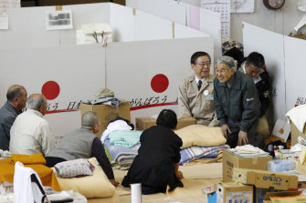 Akihito, in green, talks to evacuees after Fukushima in 2011.