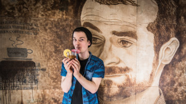 Danny Wilson, holding signature coffee cocktail 'La Leona Soda', poses in front of a portrait of Ona boss and former world barista champion Sasa Sestic.