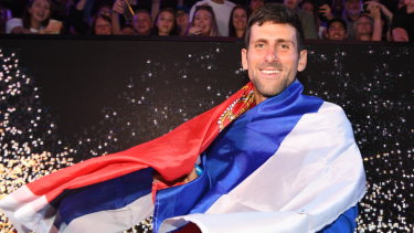 Proud moment: Djokovic swathed in the Serbian flag.