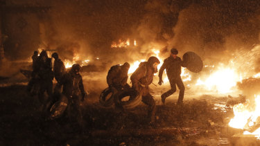 Protesters throw tyres in a fire as they clash with police in central Kiev in January 2014, during the euromaidan uprising that resulted in Yanukovych fleeing to Russia.