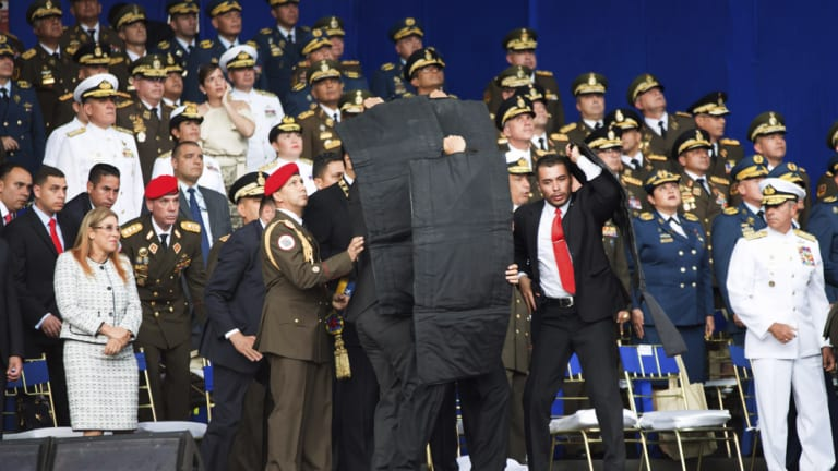 Security personnel surround Venezuela's President Nicolas Maduro during an incident as he was giving a speech in Caracas, Venezuela, on Saturday.