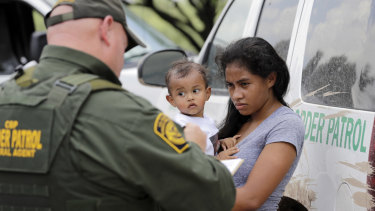 A mother migrating from Honduras holds her 1-year-old child as surrendering to U.S. Border Patrol agents after illegally crossing the border.