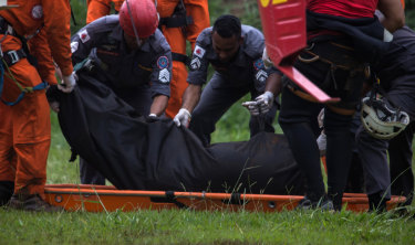 Rescue workers recover the body of a victim after the Vale SA dam burst.