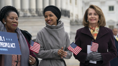 Ilhan Omar, centre, smiles as she stands between fellow Democrats Sheila Jackson Lee, left, and Speaker of the House Nancy Pelosi, outside the Capitol.