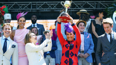 Victoria Racing Club chairman Amanda Elliott (centre), holds the Melbourne Cup aloft at Monday's launch alongside racing identities including Gai Waterhouse (third from left).
