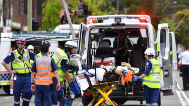 A pedestrian is taken away by paramedics at the scene of the truck crash at Green Square.