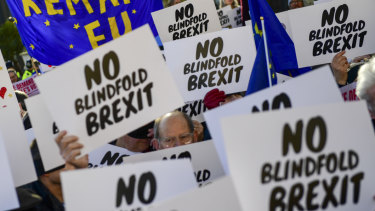 "Demonstrators calling for a second Brexit referendum hold ""No blindfold Brexit"" signs as they protest near the House of Parliament."