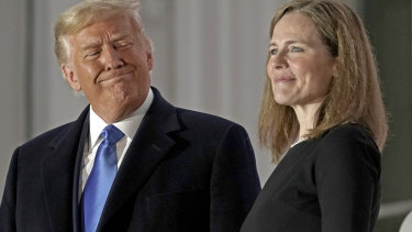 US President Donald Trump, left, rushed the appointment and swearing in of Amy Coney Barrett, associate justice of the US Supreme Court, last month.