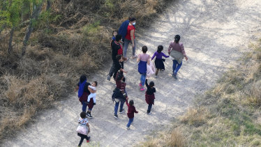 Migrants walk on a dirt road after crossing the US-Mexico border in Mission, Texas.