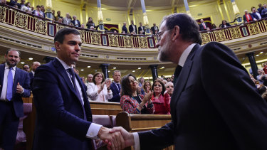 Spain's ousted Prime Minister Mariano Rajoy, right, shakes hands with socialist leader Pedro Sanchez after a motion of no confidence vote at the Spanish parliament in Madrid on Friday