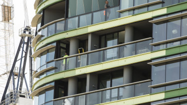 Tradespeople work on the Opal Tower at Sydney Olympic Park.