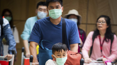 People arrive at Sydney Airport wearing masks to avoid contact with the coronavirus.