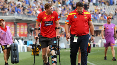 Gold Coast Sun Matt Rowell with coach Stuart Dew after injuring his knee at Optus Stadium.