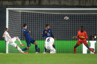 Real's Karim Benzema scores his side's equaliser against Chelsea in Madrid.