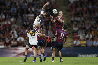 Brumbies winger Andy Muirhead reaches for the ball but Reds fullback Bryce Hegarty has it covered.