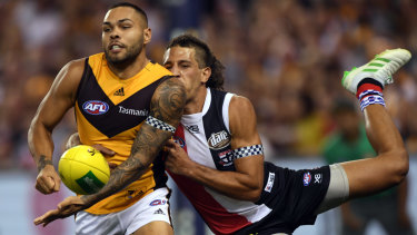Tight contest: Hawthorn's Jarman Impey (left) gives off under pressure from Saint Ben Long.