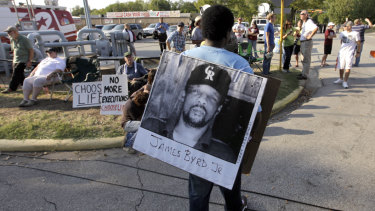 A protester carries a photograph of James Byrd jnr outside the Texas Department of Criminal Justice Huntsville Unit before the execution of Lawrence Russell Brewer in Huntsville, Texas in 2011.