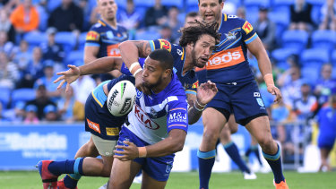 Letting loose: Ofahiki Ogden gets away an offload under pressure from Kevin Proctor at CBUS Super Stadium.