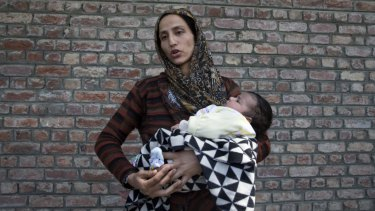 Kashmiri woman Ulfat holds her daughter as she waits outside a police station for news of her husband, who was detained during the night raids in Srinagar, Indian controlled Kashmir.