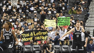 People raise signs referencing Tibet and Hong Kong during the fourth quarter of a preseason NBA basketball game between the Toronto Raptors and the Brooklyn Nets.