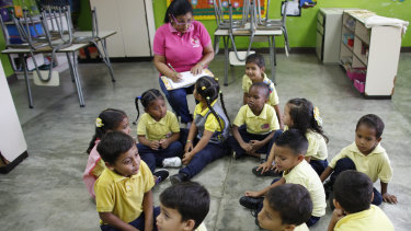 Teacher Daixy Aguero take notes as she teaches her class at a school in Caracas, Venezuela.