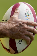 A member of Australia's men's rugby sevens team holds a ball during  a practice session in Tokyo.