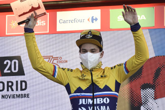Primoz Roglic celebrates his stage win on the podium.