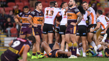 Agony and ecstasy: Brisbane players come to terms with another narrow defeat.