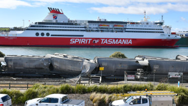 The crumpled carriages lie opposite the Spirit of Tasmania ferry.