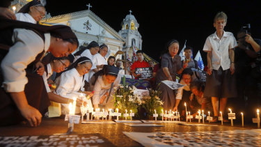 Australian nun Sister Patricia Fox, right, takes part in prayers to protest the killings of Roman Catholic priests in the Philippines.