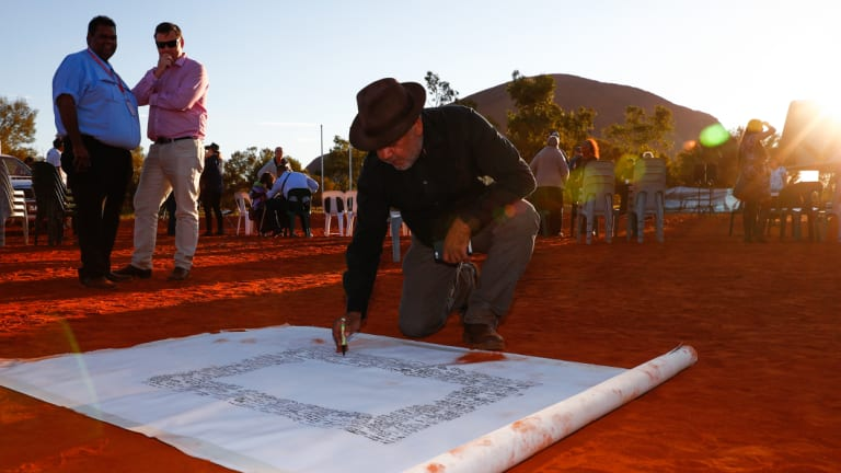 Noel Pearson signs a canvas on which the Uluru Statement from the Heart was later painted.